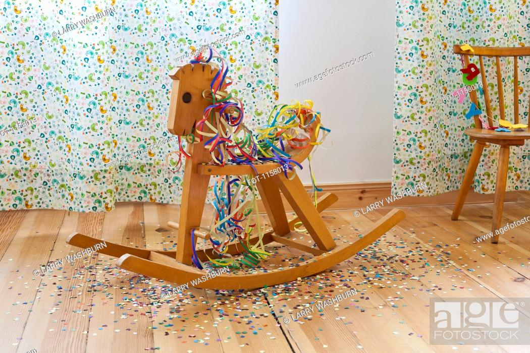 Stock Photo: A rocking horse amongst streamers, confetti and happy birthday banner.