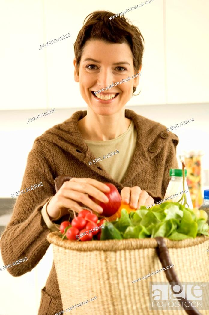 Stock Photo: Portrait of a mid adult woman smiling in the kitchen.