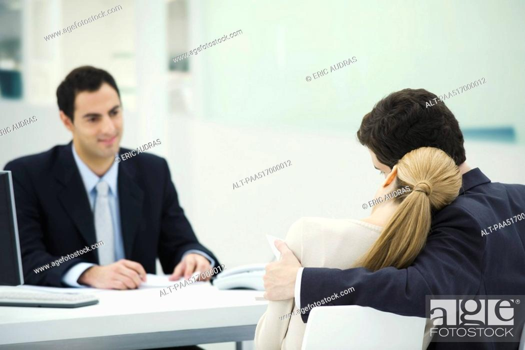 Stock Photo: Meeting between professional and clients, woman resting head on man's shoulder.