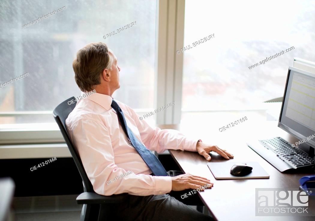 Stock Photo: Businessman gazing out window in office.