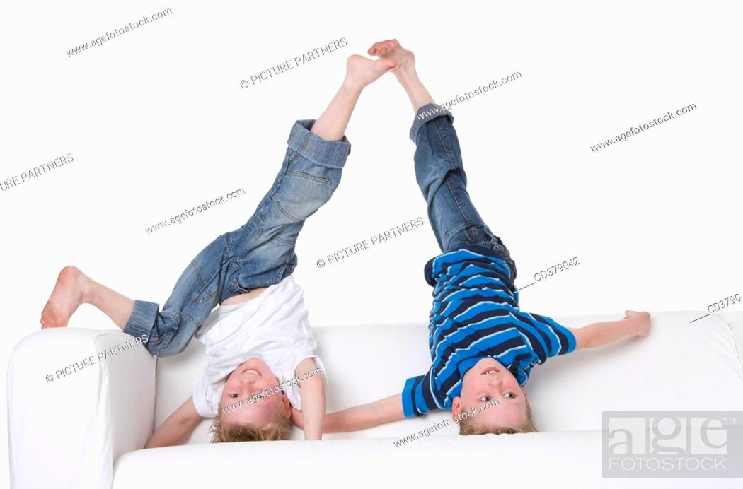 Stock Photo: Two boys climbing on a bench.