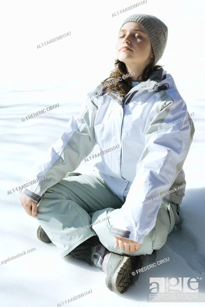 Stock Photo: Teenage girl sitting indian style on snow with eyes closed and head back, full length.