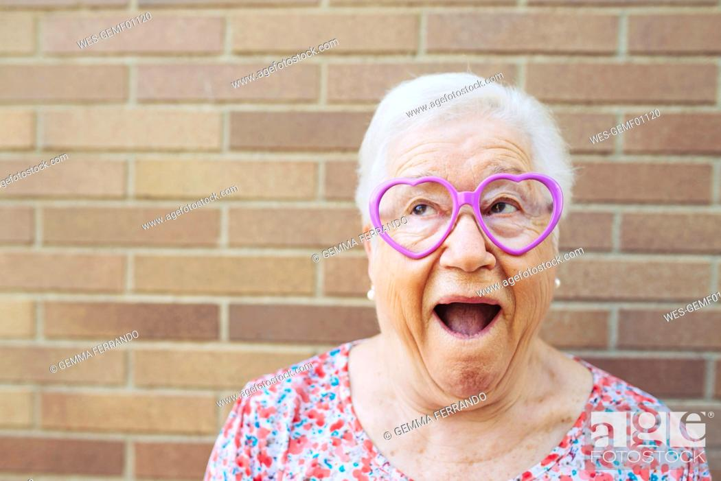 Stock Photo: Portrait of senior woman wearing heart-shaped glasses pulling funny faces.