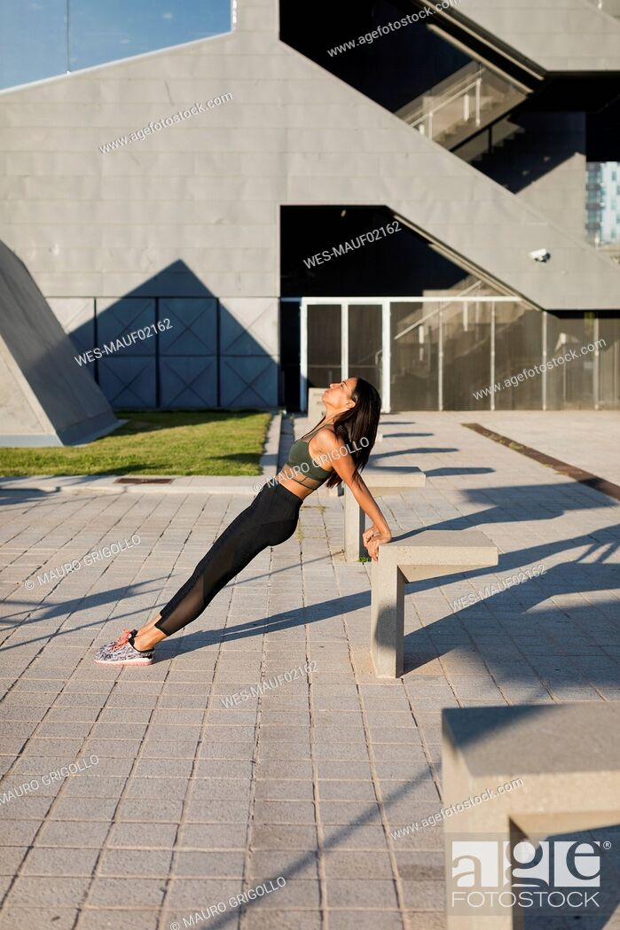 Stock Photo: Young woman doing workout exercise in the city.