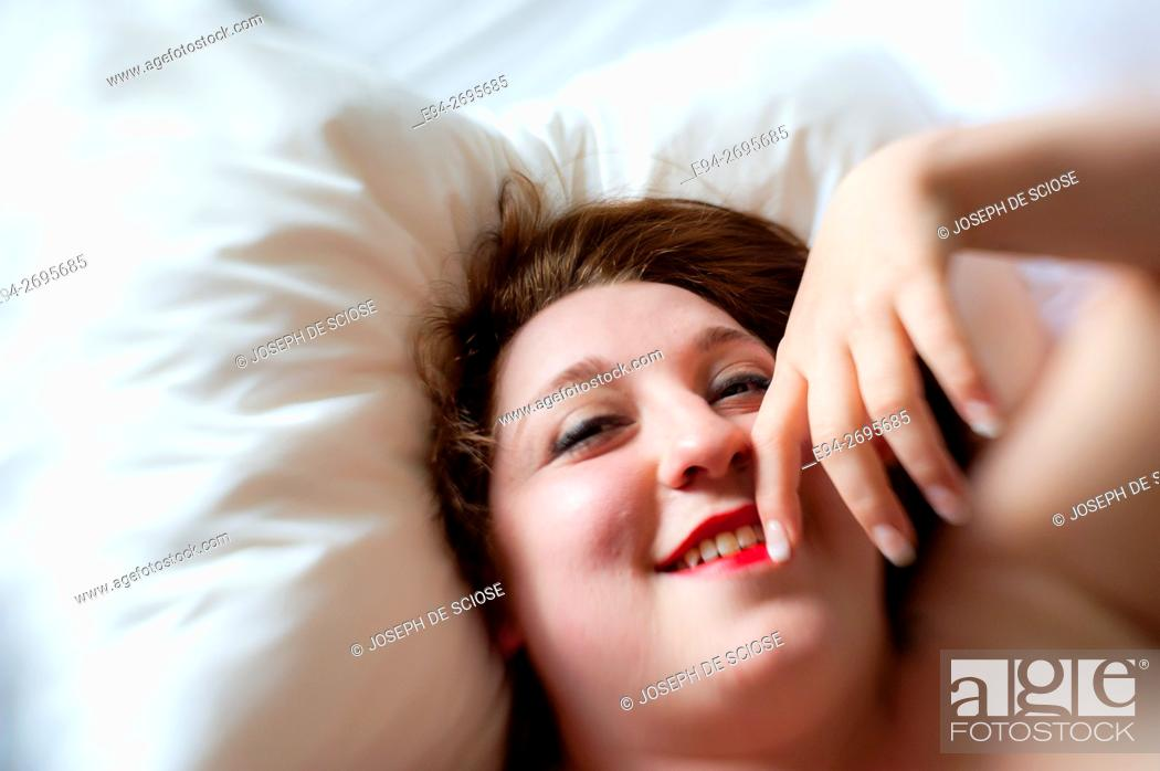 Stock Photo: Portrait of a partially nude 24 year old woman lying on a bed and smiling at the camera.