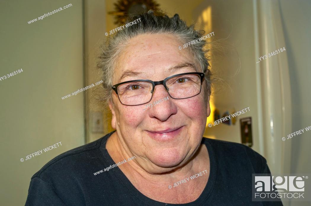 Stock Photo: Happy senior woman sitting in the kitchen.