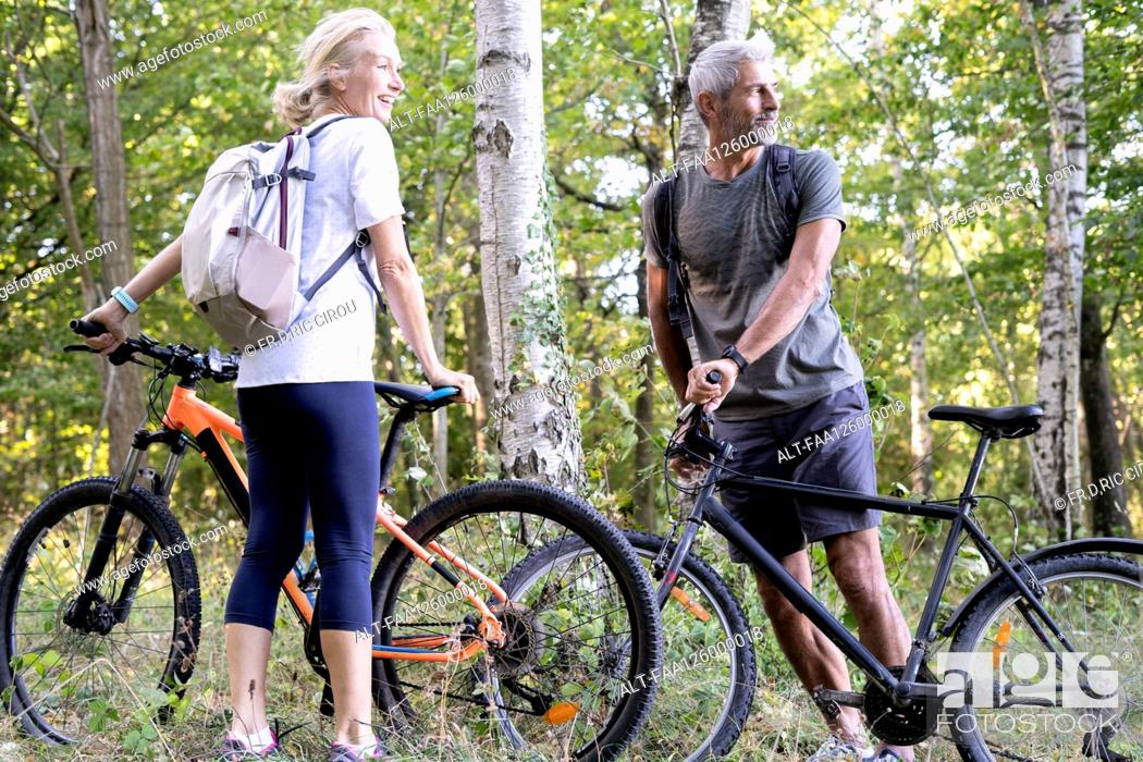 Imagen: Smiling mature couple with bicycles standing in forest.