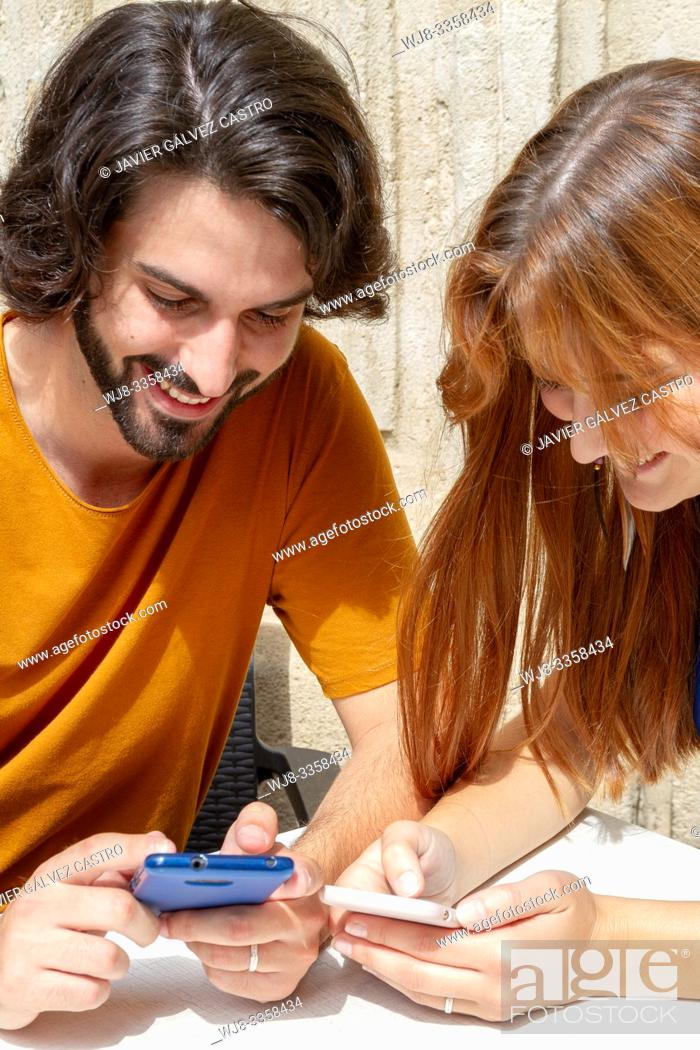 Stock Photo: Young couple looking at the mobile on a summer terrace, smile while they wait.