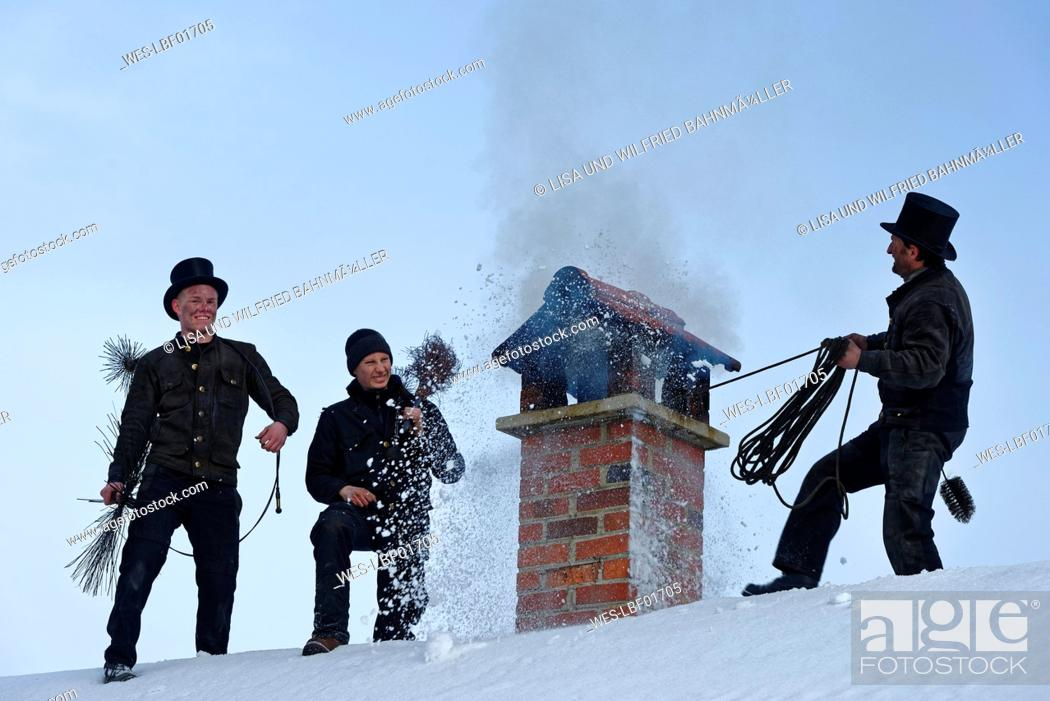 Stock Photo: Three chimney sweeps working on roof top.