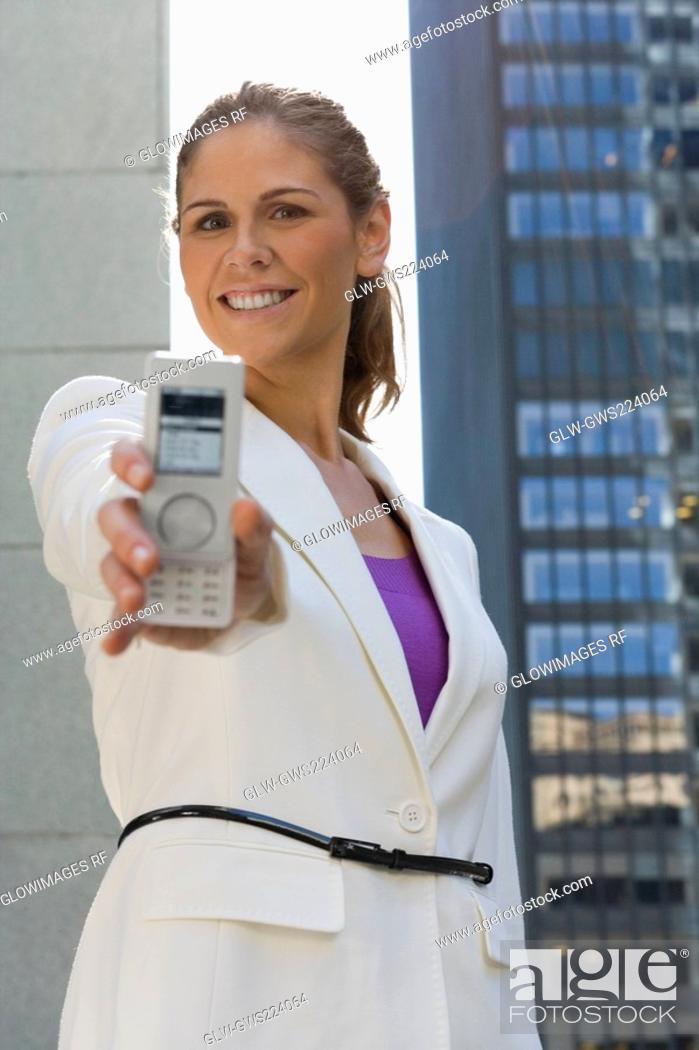 Stock Photo: Portrait of a businesswoman showing a mobile phone and smiling.