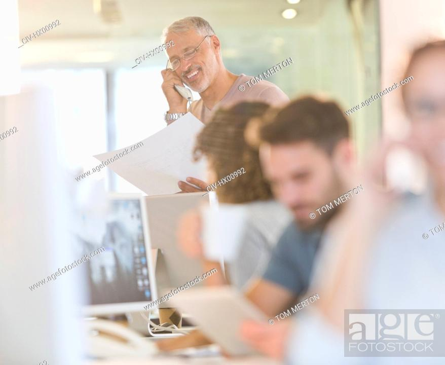 Stock Photo: Architect with blueprints talking on telephone in office.