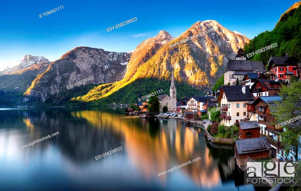Stock Photo: Classic postcard view of famous Hallstatt lakeside town reflecting in Hallstattersee lake in the Austrian Alps in scenic morning light on a beautiful sunny day.