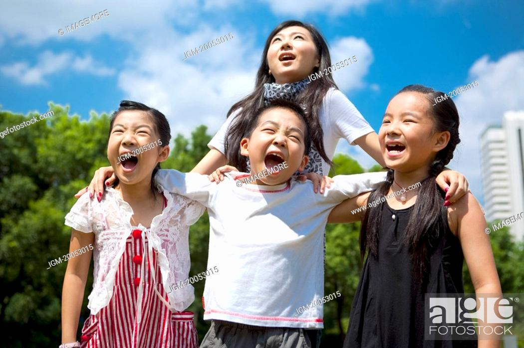 Stock Photo: A young lady standing behind three children with arms around and shouting happily.