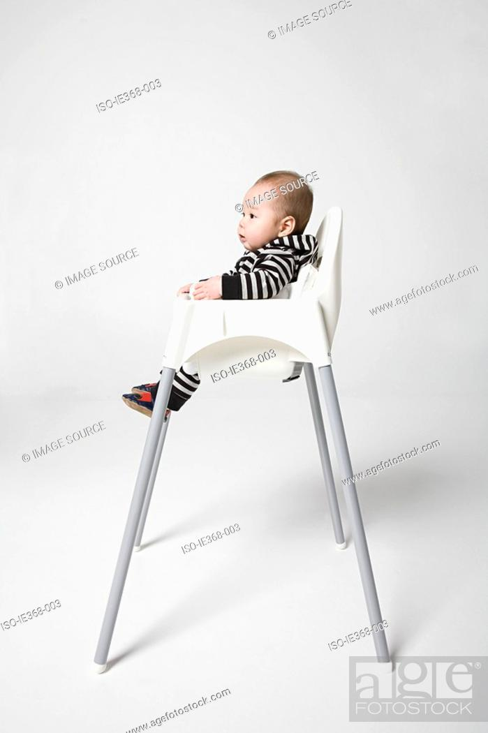 Stock Photo: A baby in a high chair.