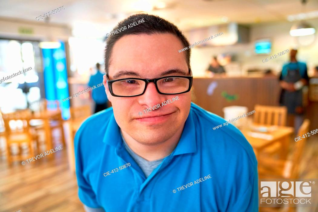 Stock Photo: Close up portrait smiling young man with Down Syndrome in cafe.
