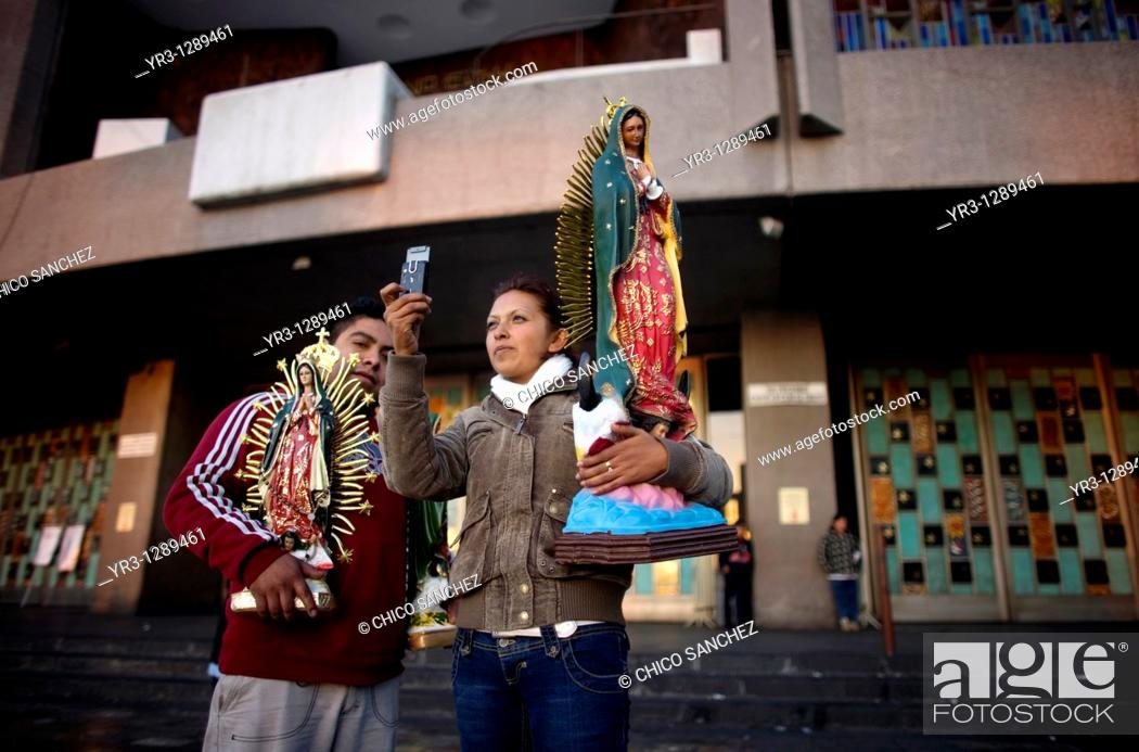 Stock Photo: A pilgrim carrying a statue of the Our Lady of Guadalupe take a picture with her cell phone outside of the Our Lady of Guadalupe Basilica in Mexico City.