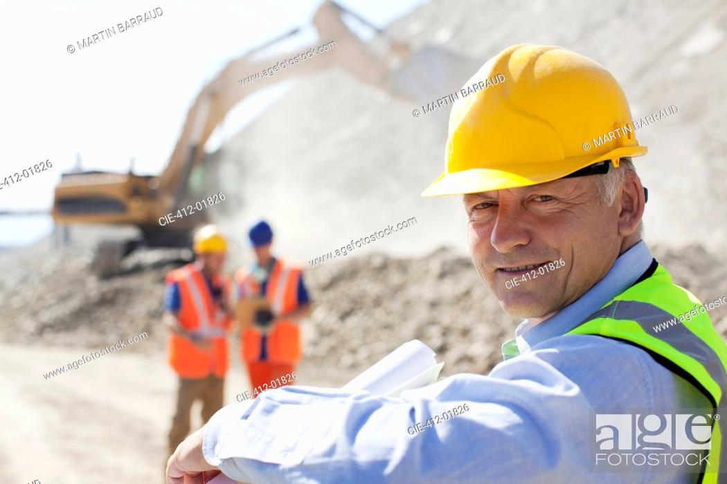 Stock Photo: Businessman wearing hard hat in quarry.
