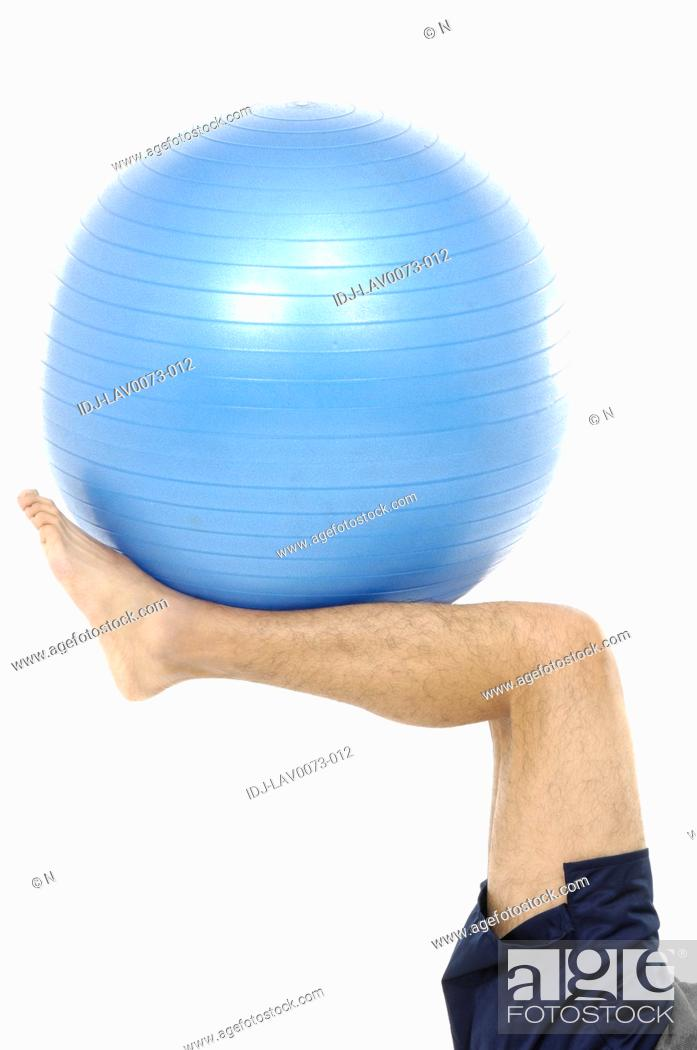 Stock Photo: Foot holding exercise ball.