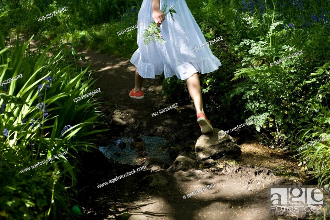 Stock Photo: Woman walking in a garden.