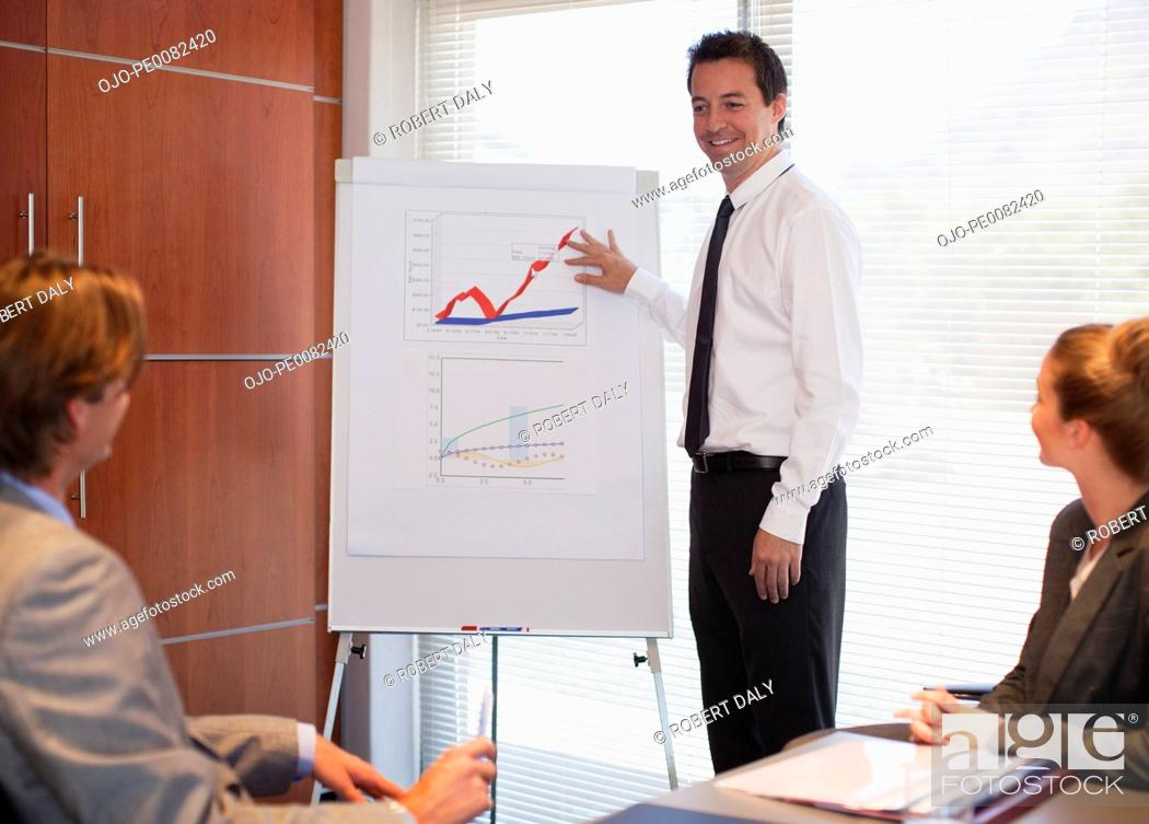 Stock Photo: Businessman pointing to flipchart in conference room.