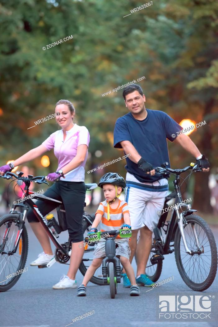 Stock Photo: portrait of happy young family with bicycles in park at night.