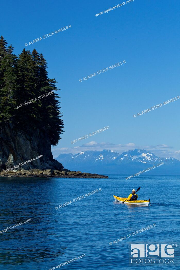 Stock Photo: Sea kayaker paddles along the shoreline near Juneau with Coast Mountains in the background, Lynn Canal, Southeast Alaska, Summer.