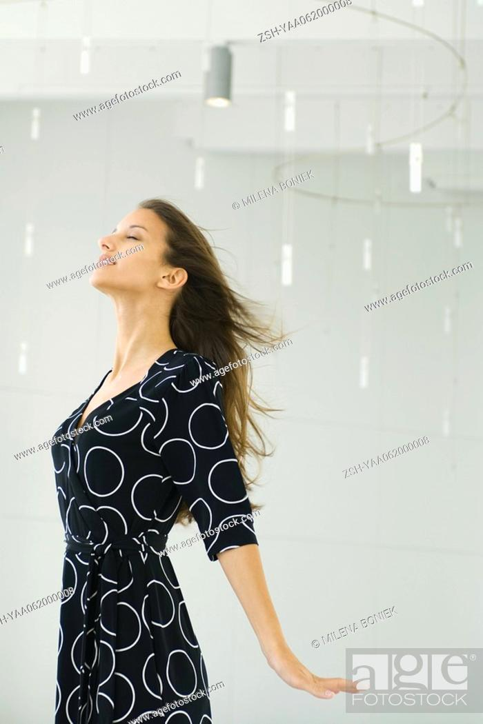 Stock Photo: Teenage girl with hair blowing in breeze, head back, eyes closed.