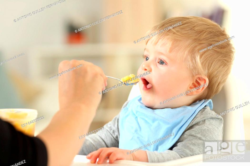 Stock Photo: Close up of a mother hand feeding her baby at home.