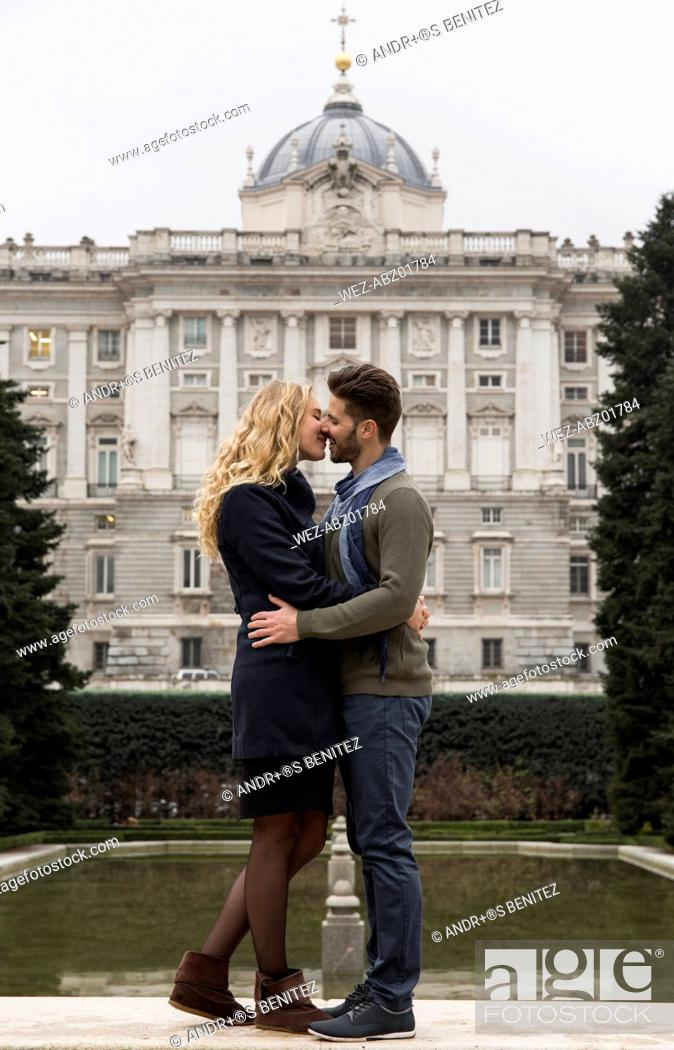 Imagen: Spain, Madrid, couple kissing with the Royal Palace in background.