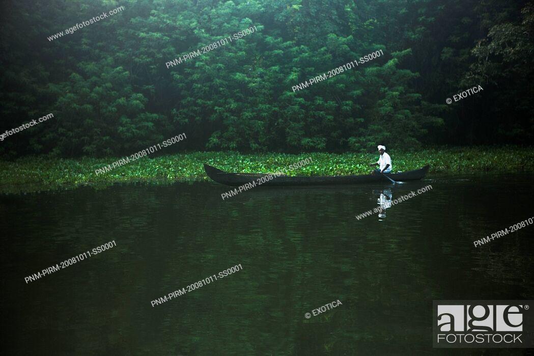 Stock Photo: Man rowing a canoe in a lagoon, Kerala Backwaters, Alappuzha District, Kerala, India.