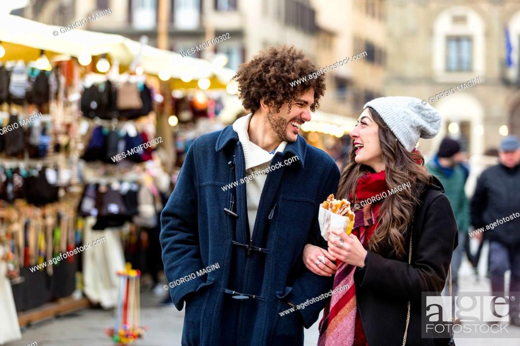 Stock Photo: Happy young couple strolling at Christmas market.