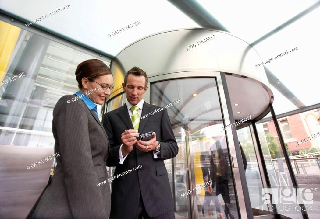 Stock Photo: Businessman showing businesswoman PDA in front of revolving door low-angle view.