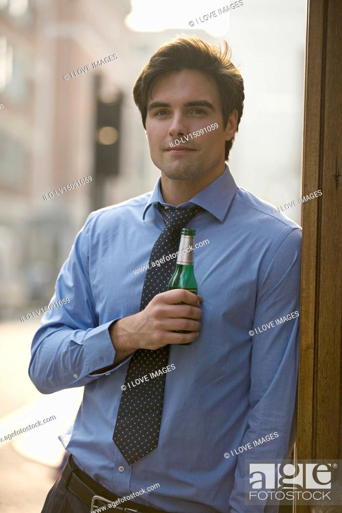 Stock Photo: A businessman holding a bottle of beer.