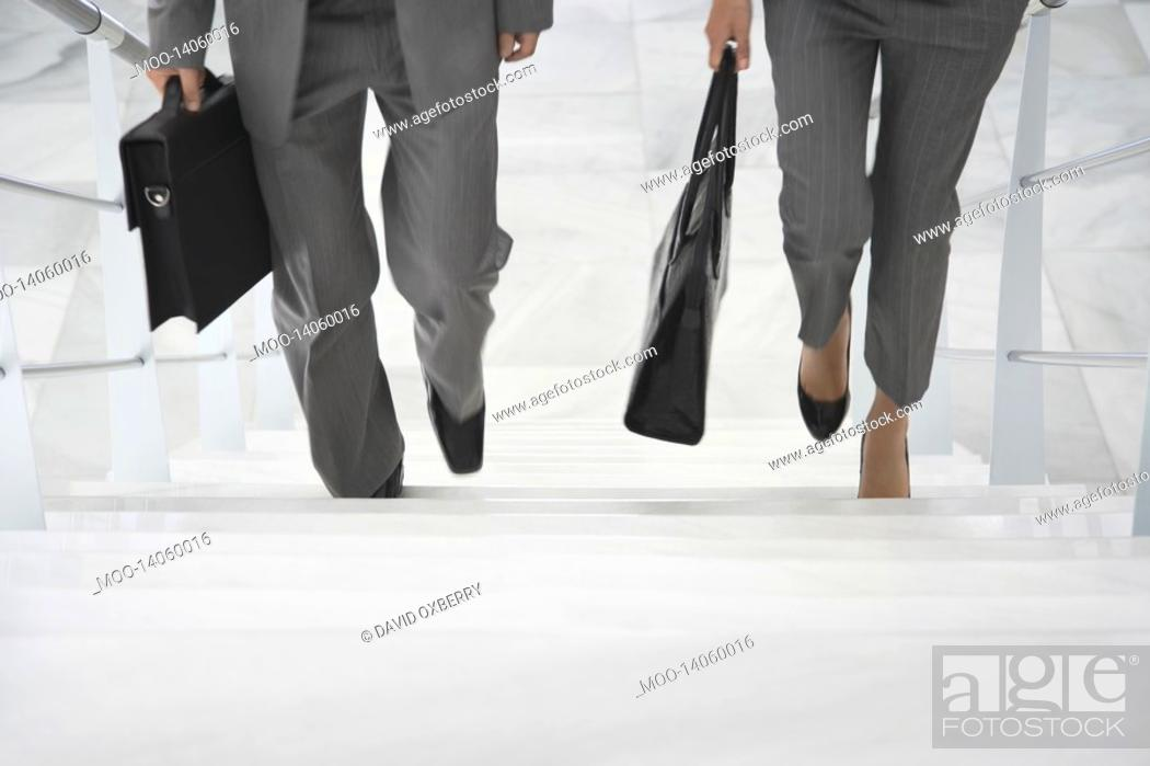 Stock Photo: Two business people walking up stairs.