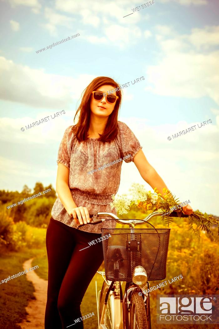 Stock Photo: Beautiful young woman and a bike in the summer fields with wildflowers on a sunny summer day.