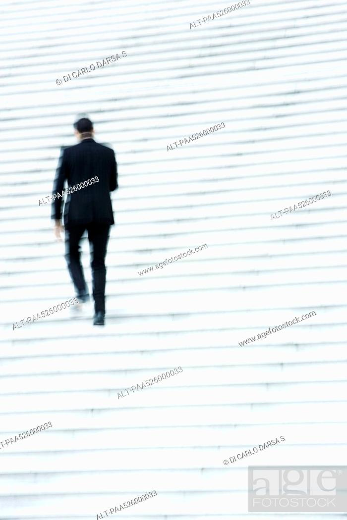 Stock Photo: Businessman ascending stairs outdoors.