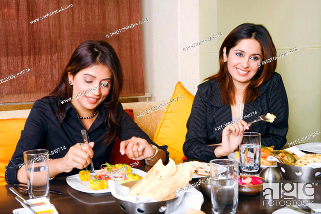 Stock Photo: Close-up of two businesswomen eating in a restaurant.
