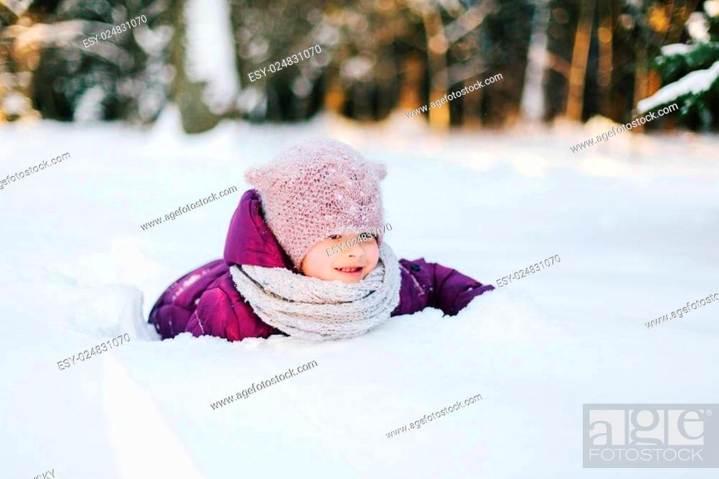 Stock Photo: Little girl playing in snowy park.