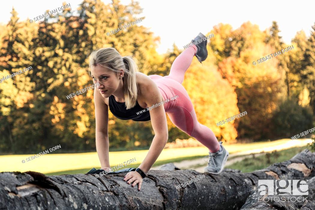 Stock Photo: Young woman doing pushups on tree trunk during workout in nature.