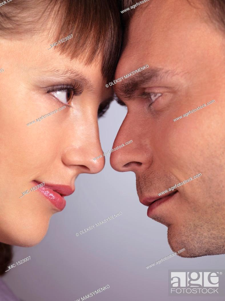 Stock Photo: Closeup portrait of a man and a woman touching foreheads and looking at each other.