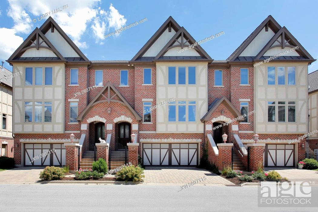 Stock Photo: Row of tudor style brick townhouses with front gates. Western Suburbs of Chicago, IL. USA.