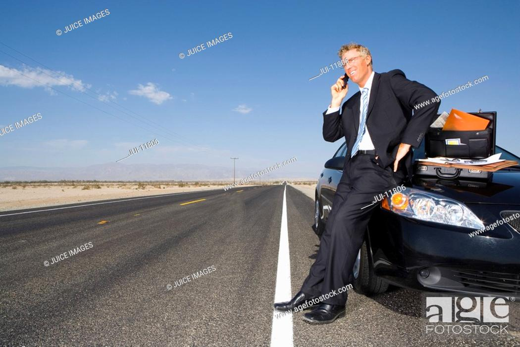Stock Photo: Businessman using mobile phone by briefcase and paperwork on car on side of road, low angle view.