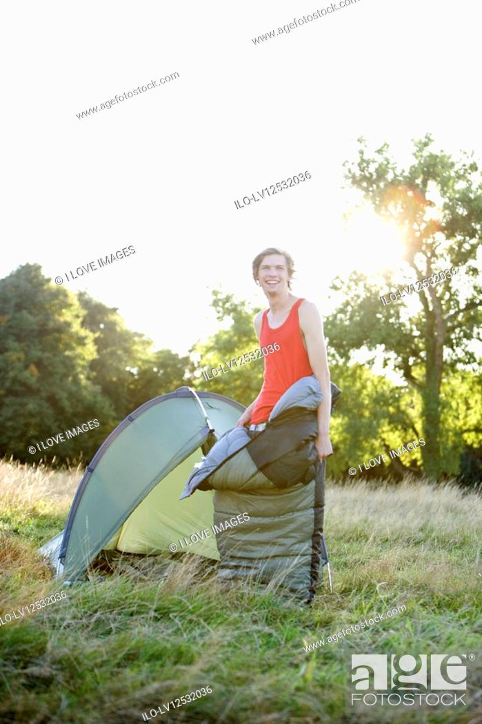 Stock Photo: A young man standing in a sleeping bag in front of a tent.