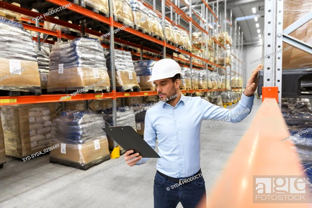Stock Photo: businessman in helmet with clipboard at warehouse.