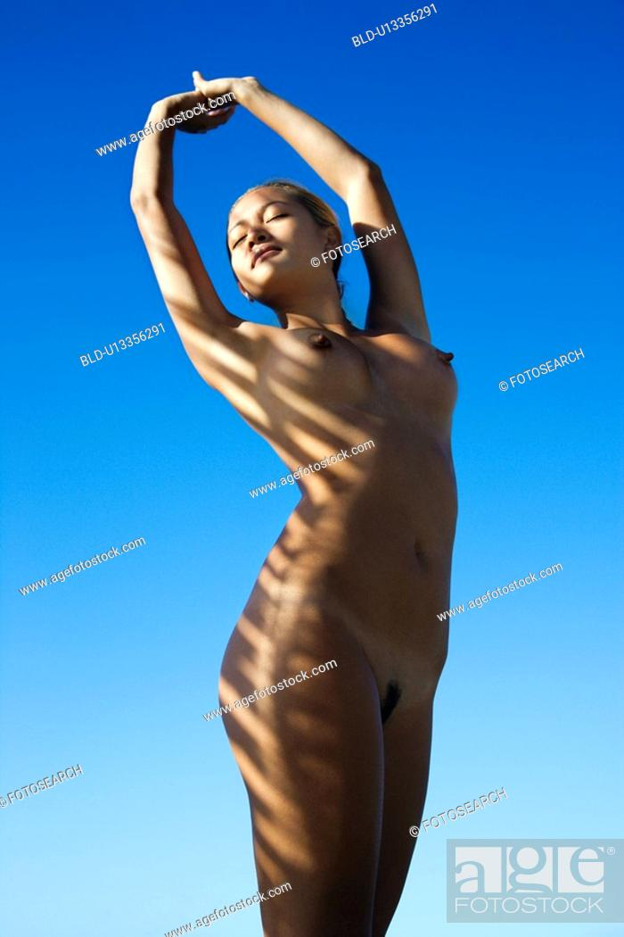 Stock Photo: Filipino young nude woman with arms stretched overhead standing with sun streaks over body.