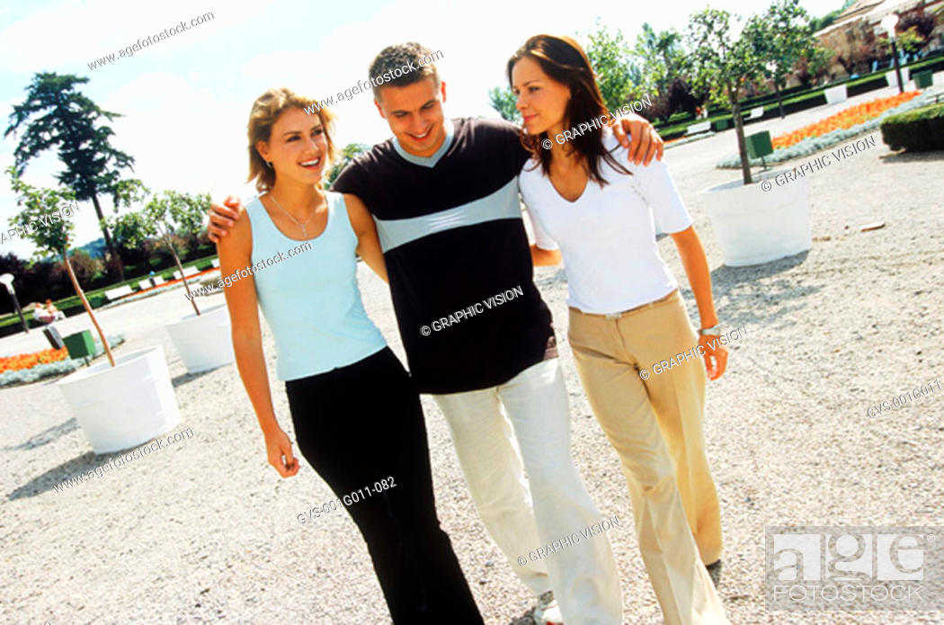 Stock Photo: Young man walking with two young women.
