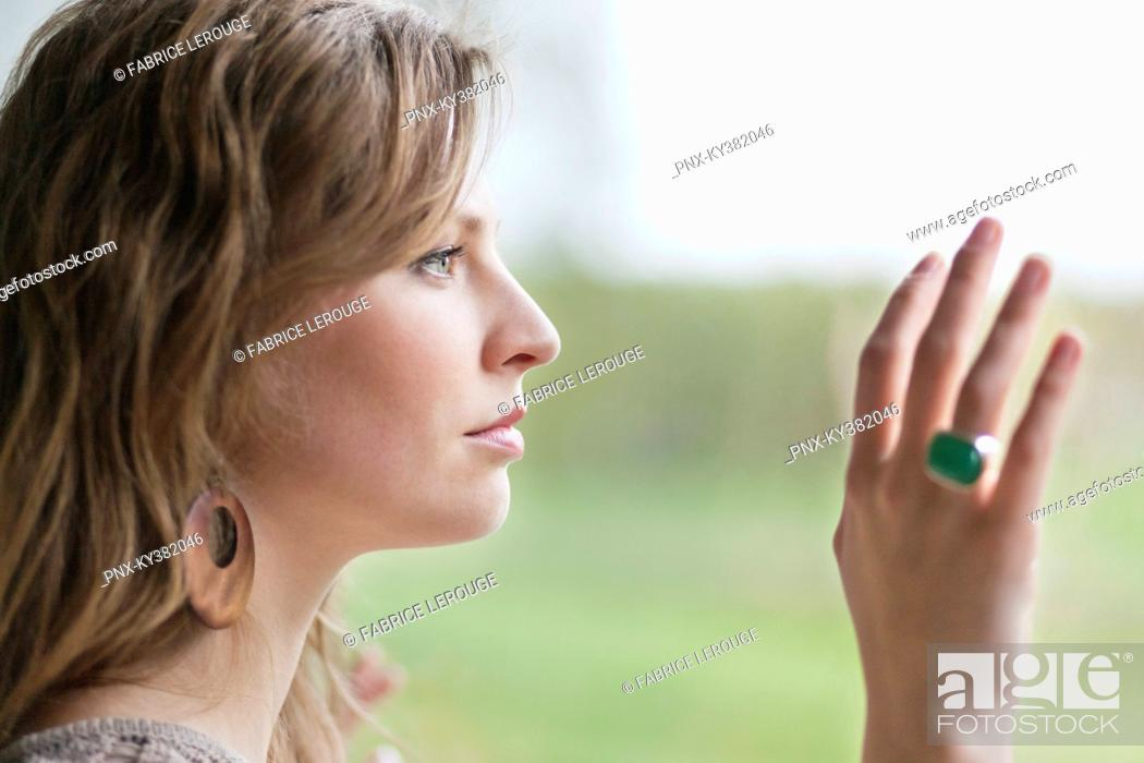 Stock Photo: Close-up of a woman looking through the glass of a window.