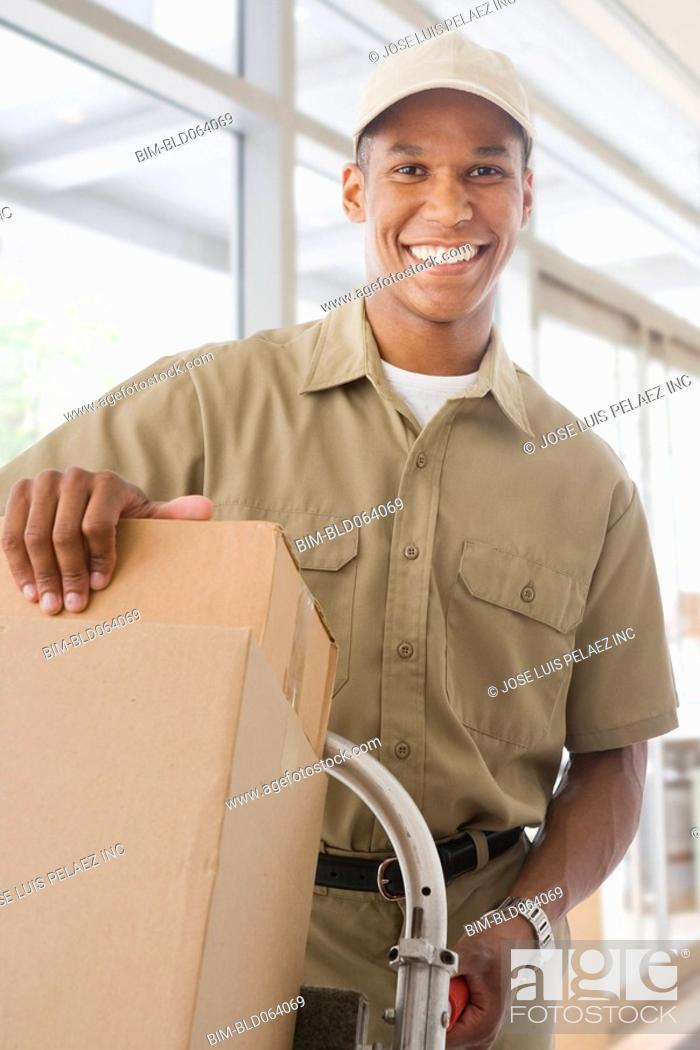 Stock Photo: Mixed race delivery man delivering boxes.