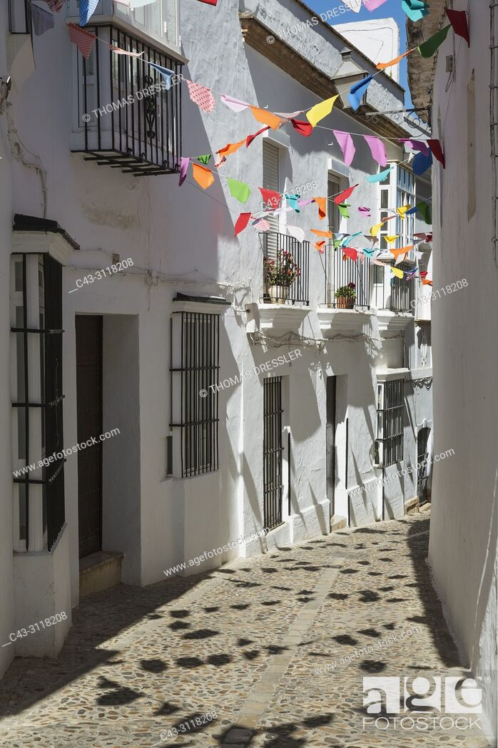 Stock Photo: Alley and brilliantly whitewashed, reja (grille) fronted houses in the hilltop White Town of Arcos de la Frontera. The little colourful flags are remains of a.
