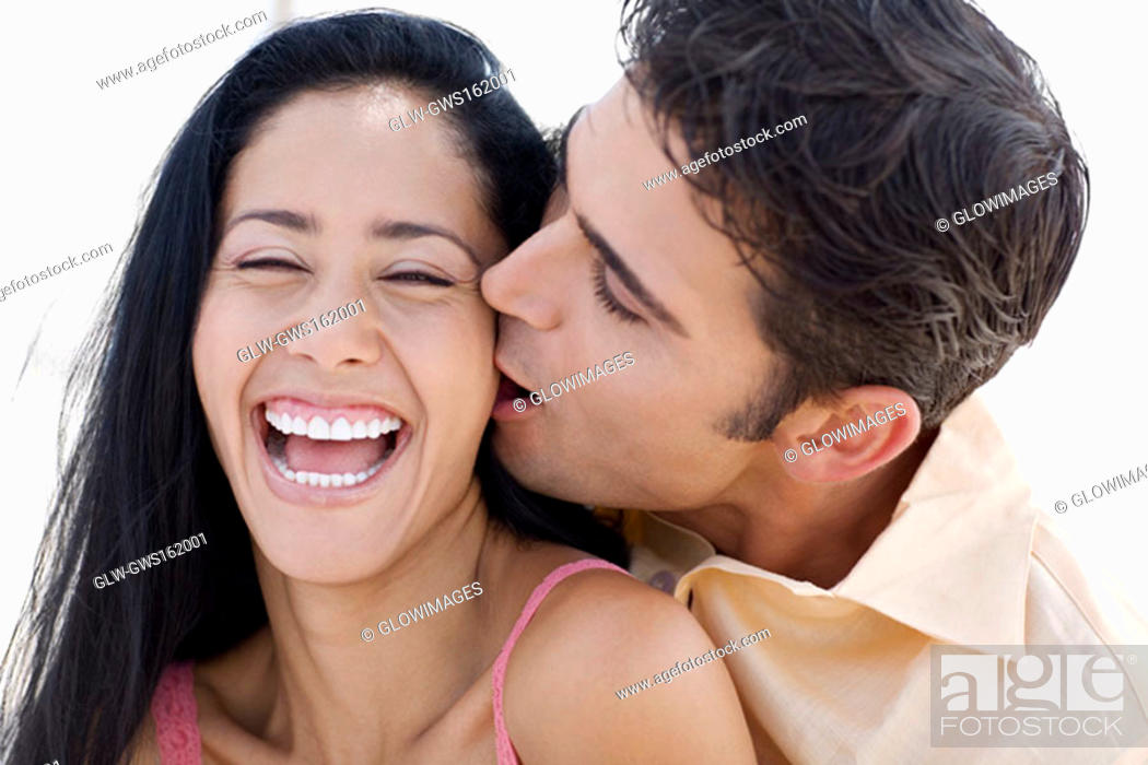 Stock Photo: Close-up of a young man kissing a young woman.